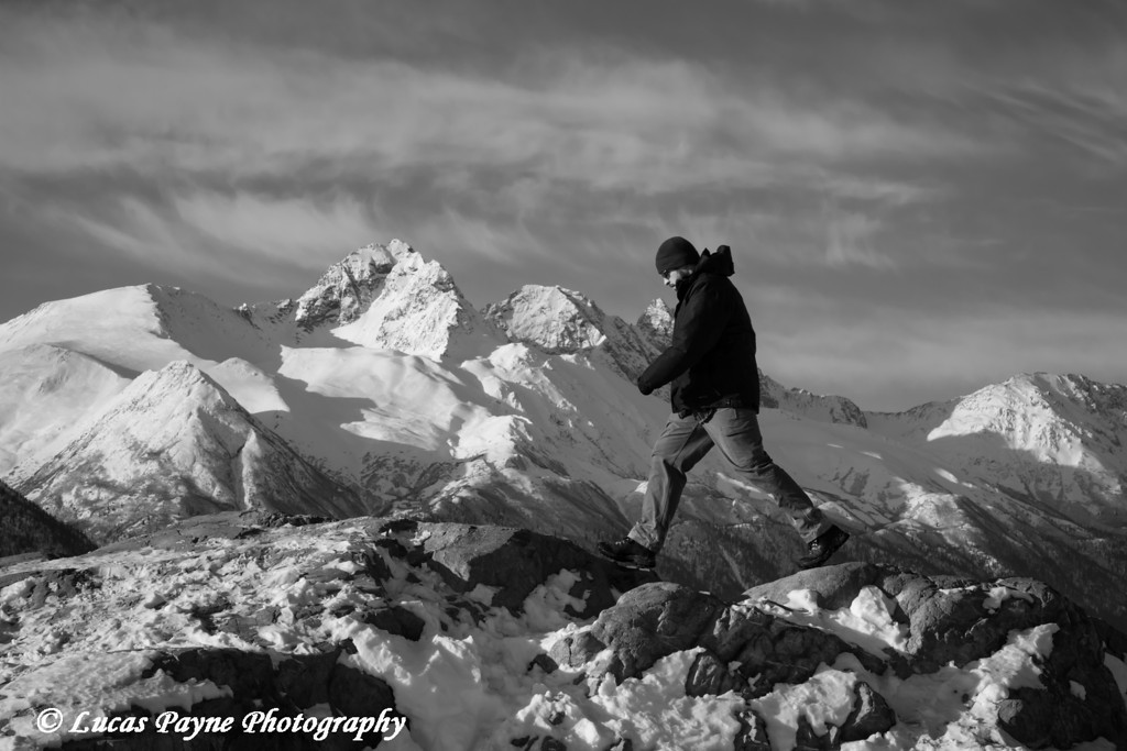 Man hiking the Bodenburg Butte with the snowcapped Chugach Mountains in the background, Matanuska Valley<br /> <br /> April 15, 2013