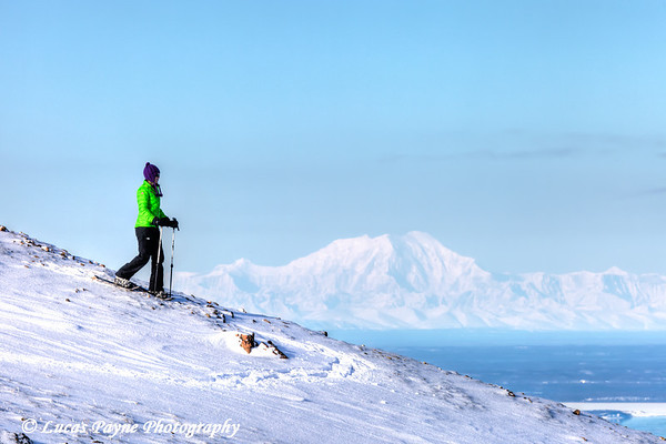 Woman snowshoeing on Blueberry Hill at the Glen Alps area of Chugach State Park with Mt. Foraker in the background, Anchorage, Alaska<br /> <br /> <br /> February 18, 2013