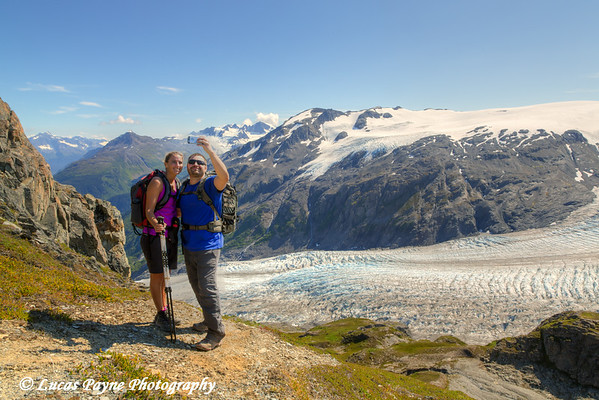 Hikers using a smart phone to take a self-portrait with Exit Glacier and the Harding Icefield in the background, Kenai Fjords National Park, Kenai Peninsula, Southcentral Alaska. <br /> <br /> August 02, 2014
