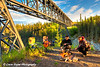 Couple roasting marshmallows over a campfire under the Kuskulana River Bridge along the McCarthy Road in Wrangell-St. Elias National Park and Preserve<br /> <br /> June 15, 2012