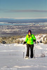 Woman snowshoeing at the Glen Alps area of Chugach State Park overlooking Anchorage on a sunny winter day<br /> <br /> February 18, 2013