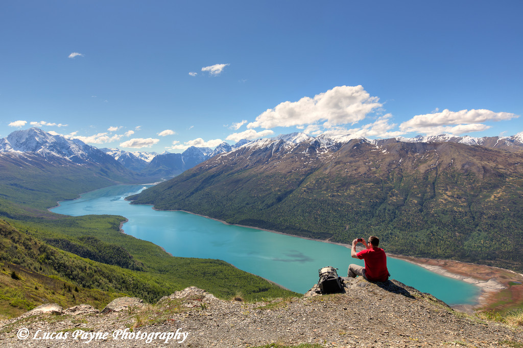 Hiker taking a picture of Eklutna Lake and the Chugach Mountains from the Twin Peaks Trail, Chugach State Park, Southcentral Alaska.<br /> <br /> June 03, 2014