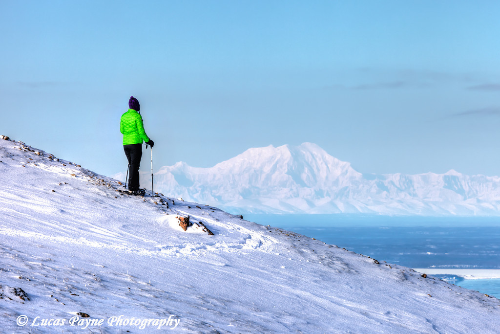Woman snowshoer taking in the view of Mt. Foraker from Blueberry Hill at the Glen Alps area of Chugach State Park, Anchorage, Alaska<br /> <br /> <br /> February 18, 2013