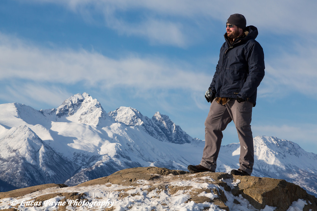 Male hiker taking in the view of the snowcapped Chugach Mountains from the Bodenburg Butte, Matanuska Valley<br /> <br /> April 15, 2013