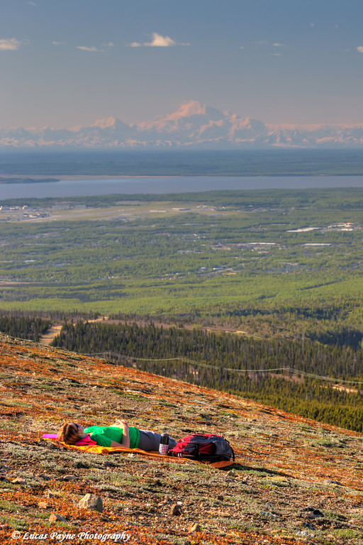 Female hiker resting on Blueberry Hill with Denali (Mt. McKinley) in the distance, Chugach State Park, Anchorage, Alaska.<br /> <br /> June 06, 2013