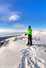 Woman snowshoer taking in the view of the Chugach Mountains from Blueberry Hill at the Glen Alps area of Chugach State Park, Anchorage, Alaska<br /> <br /> February 18, 2013