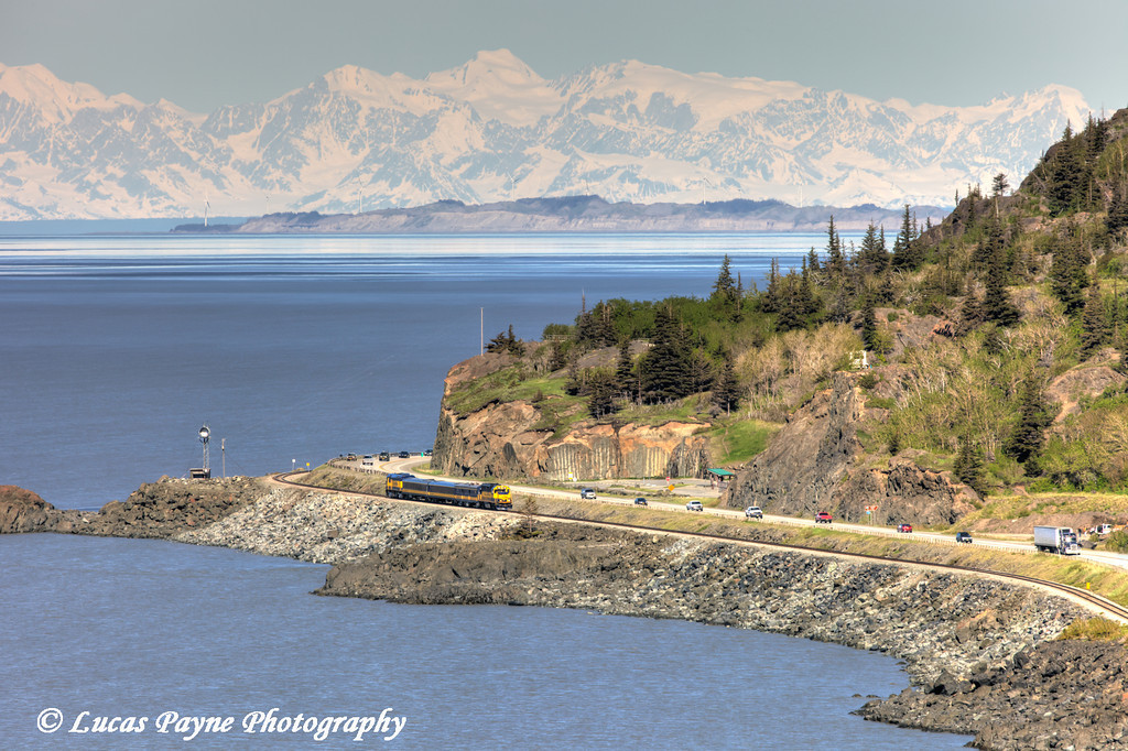 An Alaska Railroad passenger train travels along Turnagain Arm passing traffic on the Seward Highway south of Anchorage with the Alaska Range in the background.<br /> <br /> June 06, 2013