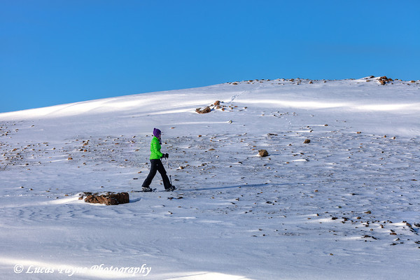 Woman snowshoeing on Blueberry Hill at the Glen Alps area of Chugach State Park, Anchorage Alaska<br /> <br /> <br /> February 18, 2013