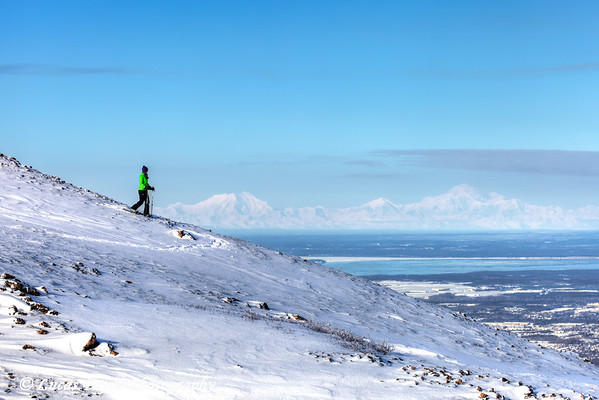 Woman snowshoeing on Blueberry Hill at the Glen Alps area of Chugach State Park with Mt. McKinley (Denali), Mt. Hunter, and Mt. Foraker in the background, Anchorage, Alaska<br /> <br /> <br /> February 18, 2013