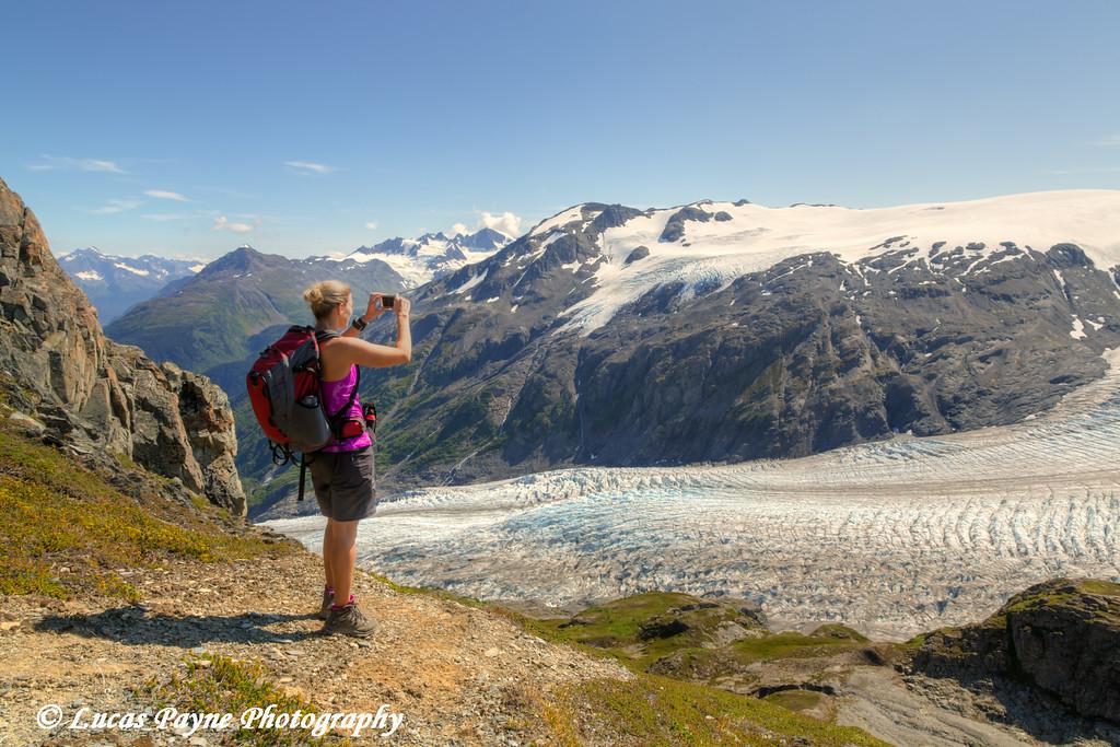 Female hiker using a smart phone to photograph Exit Glacier from the Harding Icefield Trail near Seward, Kenai Fjords National Park, Kenai Peninsula, Southcentral Alaska. <br /> <br /> August 02, 2014