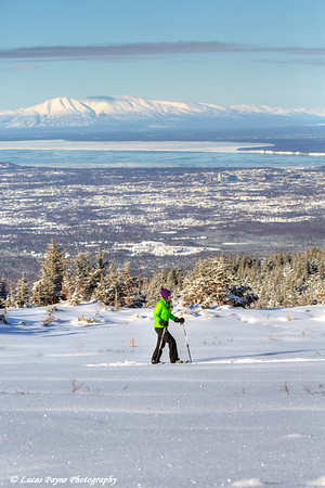 Woman snowshoeing at the Glen Alps area of Chugach State Park overlooking Anchorage with Mt. Susitna in the background on a sunny winter day<br /> <br /> February 18, 2013