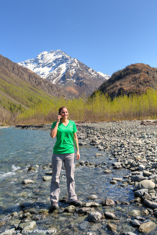 Female hiker talking on a cell phone along the East Fork Eklutna River and Chugach Mountains, Chugach State Park, Alaska.<br /> <br /> May 11, 2014