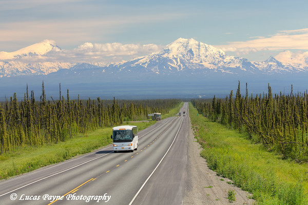 Tour Bus travelling on the scenic Glenn Highway near Glennallen with Mt. Drum and the Wrangell Mountains in the background, Southcentral Alaska.<br /> <br /> July 05, 2014
