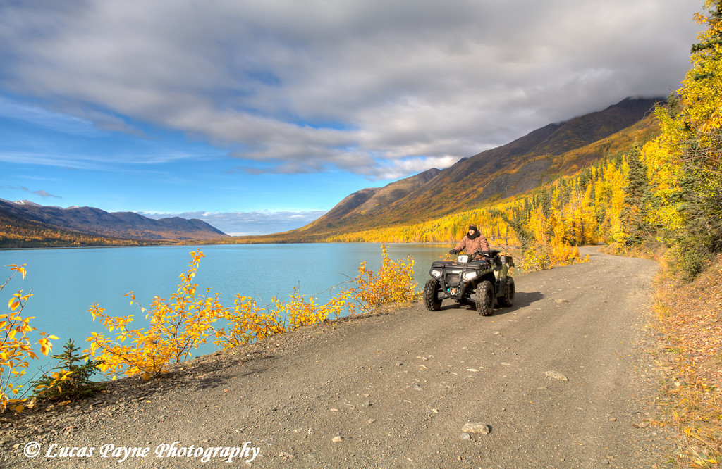 Woman riding an ATV along the Eklutna Lakeside Trail on a colorful fall day, Eklutna Lake, Southcentral Alaska.<br /> <br /> September 29, 2013