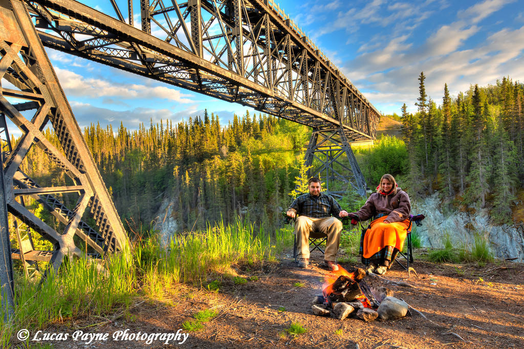 Couple sitting by a campfire holding hands under the Kuskulana River Bridge along the McCarthy Road in Wrangell-St. Elias National Park and Preserve<br /> <br /> June 15, 2012