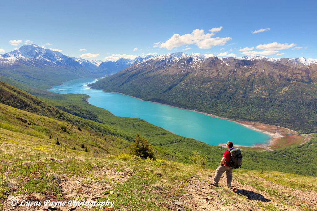 Hiker taking in the view Eklutna Lake and the Chugach Mountains from the Twin Peaks Trail, Chugach State Park, Southcentral Alaska.<br /> <br /> June 03, 2014