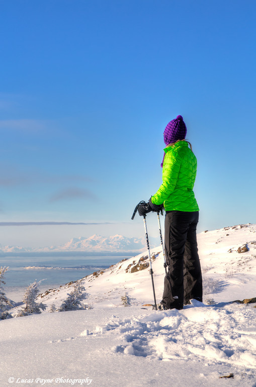 Woman snowshoer taking in the view of Cook Inlet and the Alaska Range from Blueberry Hill at the Glen Alps area of Chugach State Park, Anchorage, Alaska<br /> <br /> February 18, 2013