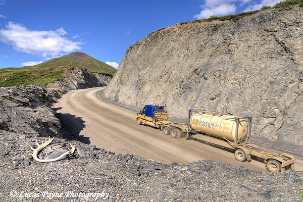 Semi truck driving on the Haul Road (James Dalton Highway) at Chandalar Shelf in the Brooks Range, Arctic Alaska.<br /> <br /> July 03, 2013