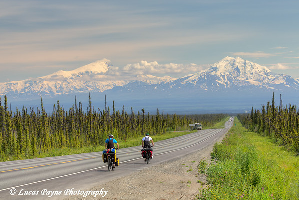 Cyclists on the Glenn Highway near Glennallen with Mt. Drum and the Wrangell Mountains in the background, Southcentral Alaska.<br /> <br /> July 05, 2014