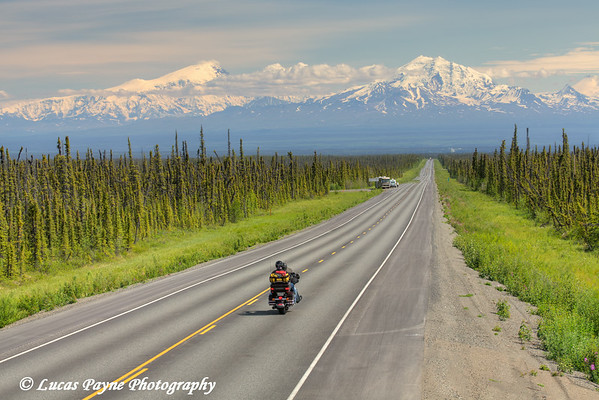 Motorcycle travelling on the scenic Glenn Highway near Glennallen with Mt. Drum and the Wrangell Mountains in the background, Southcentral Alaska.<br /> <br /> July 05, 2014