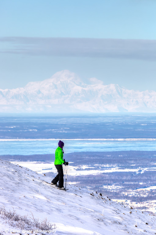 Woman snowshoeing on Blueberry Hill at the Glen Alps area of Chugach State Park with Mt. McKinley (Denali) in the background<br /> Anchorage, Alaska<br /> <br /> February 18, 2013