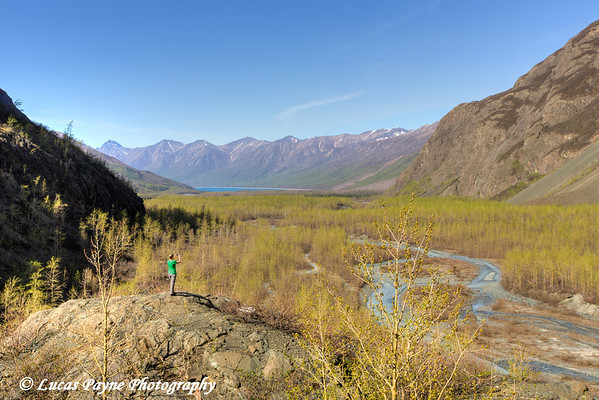 Female hiker photographing the West Fork of Eklutna River and Chugach Mountains with a smart phone, Chugach State Park, Alaska.<br /> <br /> May 11, 2014