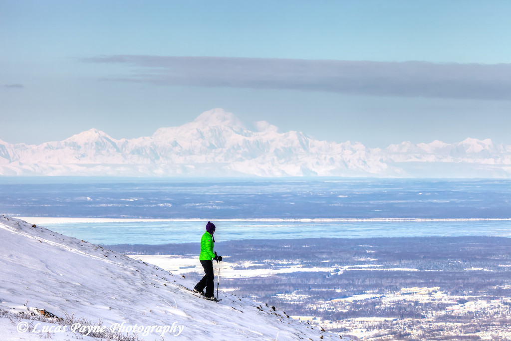 Woman snowshoeing on Blueberry Hill at the Glen Alps area of Chugach State Park with Mt. McKinley (Denali) in the background, Anchorage, Alaska<br /> <br /> February 18, 2013