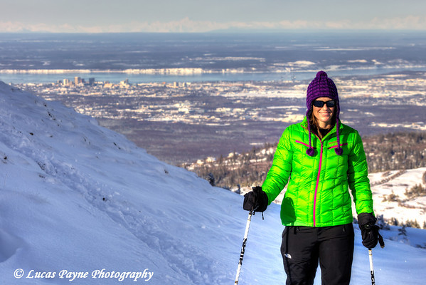 Woman snowshoeing on Blueberry Hill at the Glen Alps area of Chugach State Park overlooking Anchorage, Alaska<br /> <br /> February 18, 2013