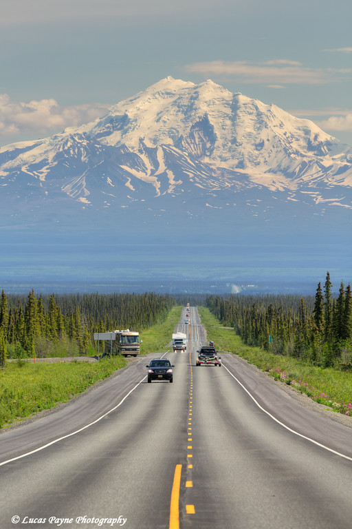 Traffic on the scenic Glenn Highway near Glennallen with Mt. Drum and the Wrangell Mountains in the background, Southcentral Alaska.<br /> <br /> July 05, 2014
