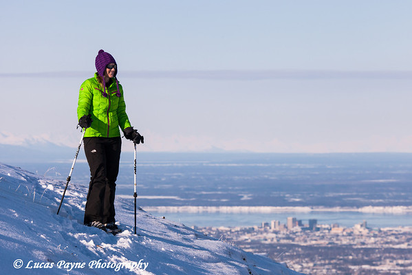 Woman snowshoer taking in the view from Blueberry Hill  at the Glen Alps area of Chugach State Park overlooking Anchorage, Alaska<br /> <br /> February 18, 2013