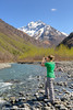 Female hiker photographing the East Fork Eklutna River and Chugach Mountains with a smart phone, Chugach State Park, Alaska.<br /> <br /> May 11, 2014