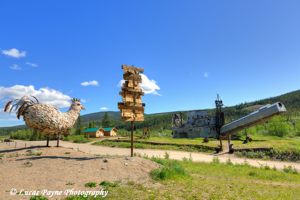 Metal Chicken Sculpture, Sign Post, and Gold Dredge at Chicken Gold Camp along the Taylor Highway, Alaska.<br /> <br /> June 28, 2014