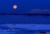 Moonrise over mount Susitna and the frozen harbor in Anchorage.