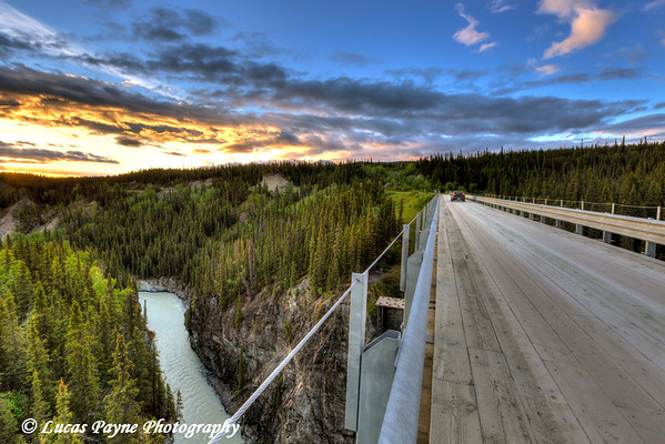 Car driving across the Kuskulana River Bridge at sunset on the McCarthy Road in Wrangell-St. Elias National Park and Preserve<br /> <br /> June 15, 2012