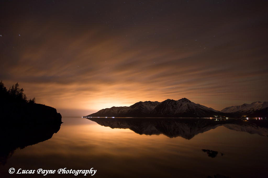 The Chugach Mountains and glow of the city lights of Anchorage reflected in the calm waters of Turnagain Arm<br /> April 13, 2012