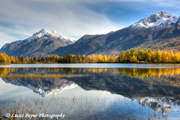 The snowcapped Chugach Mountains and fall foliage reflecting in Reflections Lake along the Glenn Highway in the Matanuska Susitna Valley, Southcentral Alaska.<br /> <br /> September 28, 2013