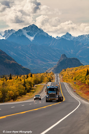 Semi and car travelling on the Glenn Highway with Lion's Head Mountain and the Chugach Mountains in the background<br /> September 08, 2011