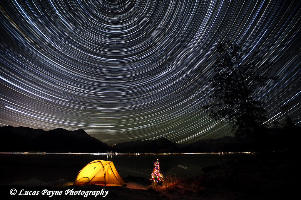 Star trails circle above the Chugach Mountains with a backpacking tent and Christmas Tree along the shore of Turnagain Arm, Kenai Peninsula, Alaska.<br /> <br /> January 21, 2015