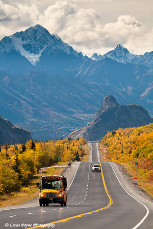 School Bus and truck travelling on the Glenn Highway with Lion's Head Mountain and the Chugach Mountains in the background<br /> September 08, 2011