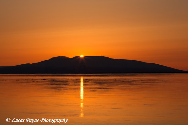 The sun setting behind Mt. Susitna (The Sleeping Lady) and reflecting in Cook Inlet from Point Woronzof<br /> Anchorage, Alaska<br /> <br /> May 08, 2013