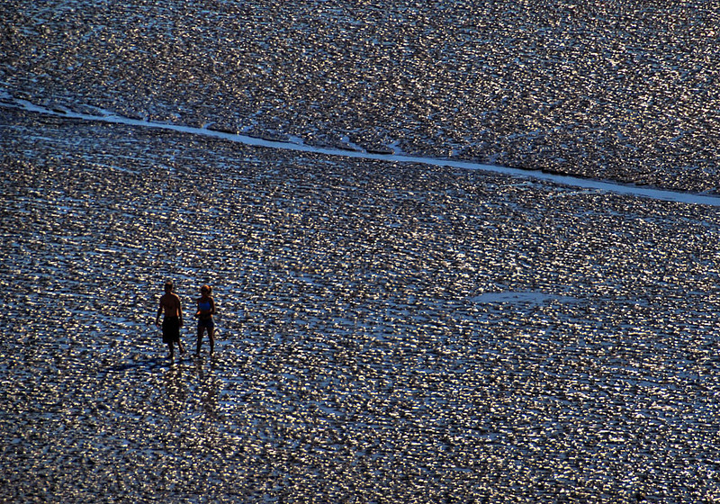 Couple walking on mudflats near Kincaid Park