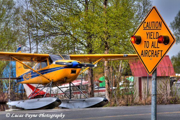 """Caution Yield To All Aircraft"" sign and Floatplane along Lakeshore Drive at Lake Hood in Anchorage<br /> May 19, 2011<br /> HDR"
