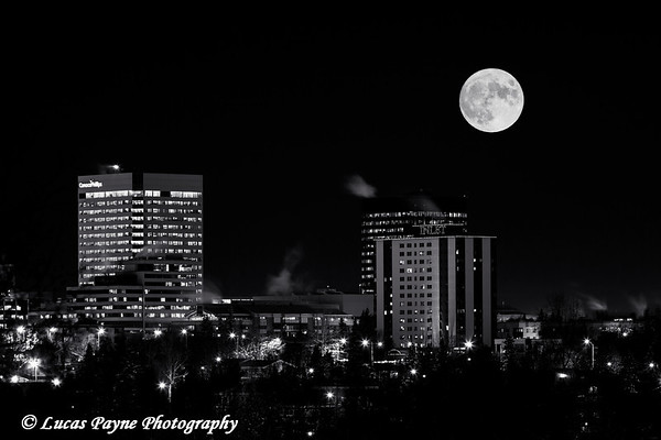 A full moon hovers over the skyline of downtown Anchorage, Southcentral Alaska.<br /> <br /> December 16, 2013