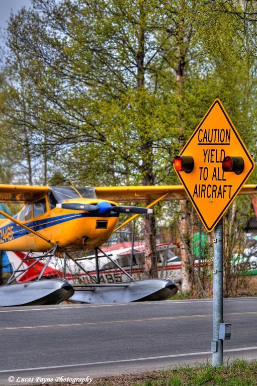 """""""Caution Yield To All Aircraft"""" sign and Floatplane along Lakeshore Drive at Lake Hood in Anchorage<br /> May 19, 2011<br /> HDR"""