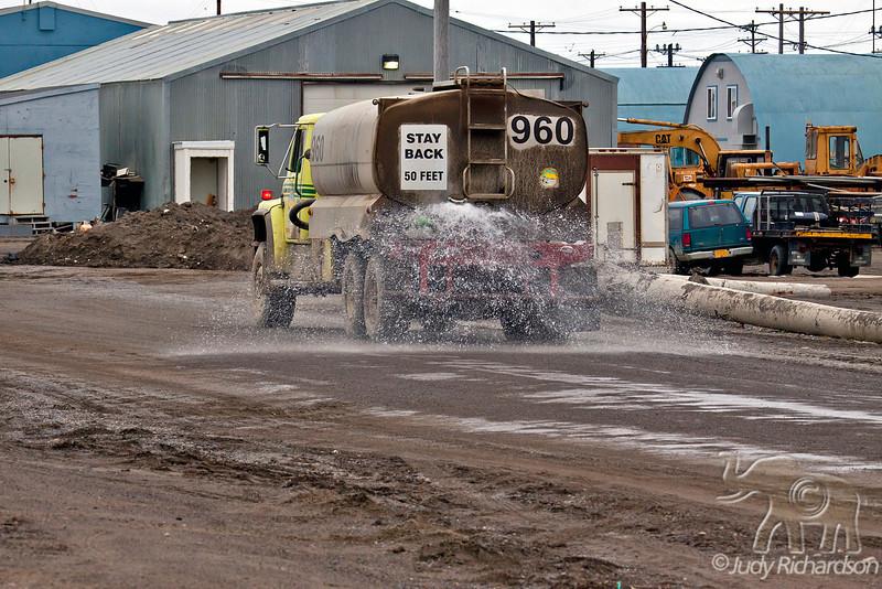 Watering already muddy road in Barrow, Alaska.