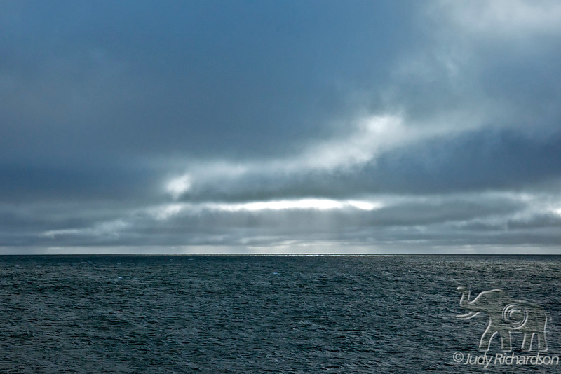 Late night rays of sun streaming through clouds over the Arctic Ocean in Barrow, Alaska