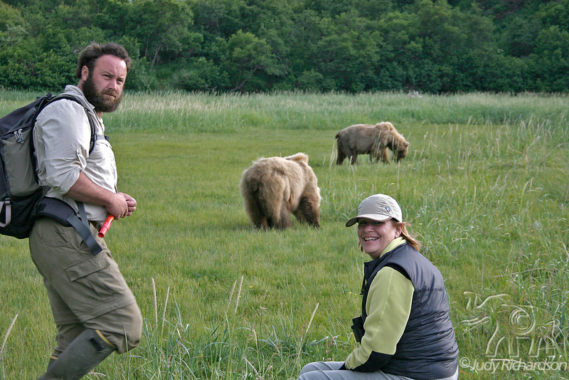Guide with flare ready and visitor observing bears