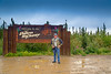 Dalton Highway sign with Alan Richardson posing in the mud!