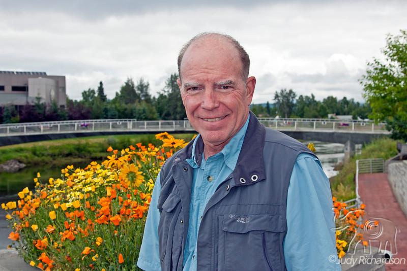 Alan with Chena River, bridge, and flowers in Fairbanks, Alaska