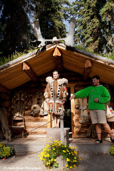 Alaskan Native Indian guide modeling a fur coat outside a cabin at an Athabascan village on the Riverboat Discovery Tour. Fairbanks, Alaska<br /> August 06, 2011